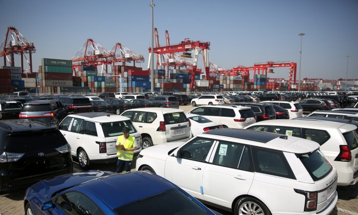 A worker inspects imported cars at a port in Qingdao, Shandong Province, China on May 23, 2018. (Reuters)
