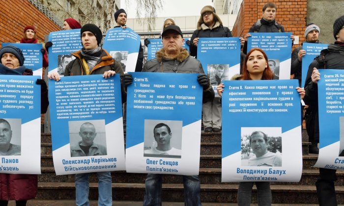 Activists hold pictures of 70 Ukrainian political prisoners jailed in Russia (including the sailors taken in the Azov Sea conflict) during a rally in front of the EU Embassy in Kiev on Dec. 11, 2018. (SERGEI SUPINSKY/AFP/Getty Images)