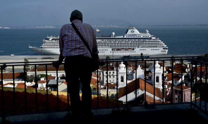 A man looking at a cruise ship from a viewpoint in the Alfama neighborhood of Lisbon, on April 15, 2014. (Patricia de Melo Moreira/AFP/Getty Images)