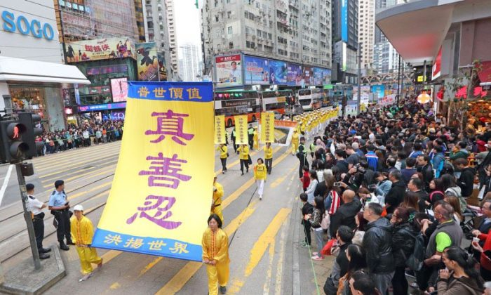 Falun Gong practitioners hold up yellow banners in a parade in Hong Kong on Dec. 9, 2018. (Li Yi/The Epoch Times)