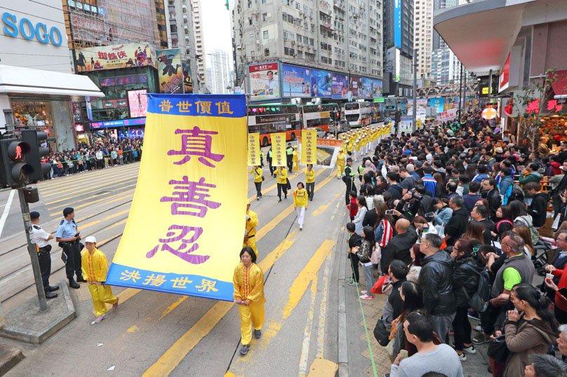 """Obyvatelé Hongkongu, kteří se věnují meditační praxi Falun Gong, nesou v ulicích města žluté transparenty s morálními principy Falun Gongu: """"Pravdivost, soucit a snášenlivost"""". Hongkong 9. prosince 2018. (Li Yi / The Epoch Times)"""