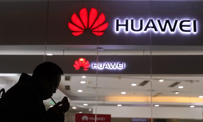A man lights a cigarette outside a Huawei retail shop in Beijing on Dec. 6, 2018. Taiwan is reinforcing its five-year-old ban on network equipment produced by Chinese companies Huawei and ZTE amid security concerns. (Ng Han Guan/AP)