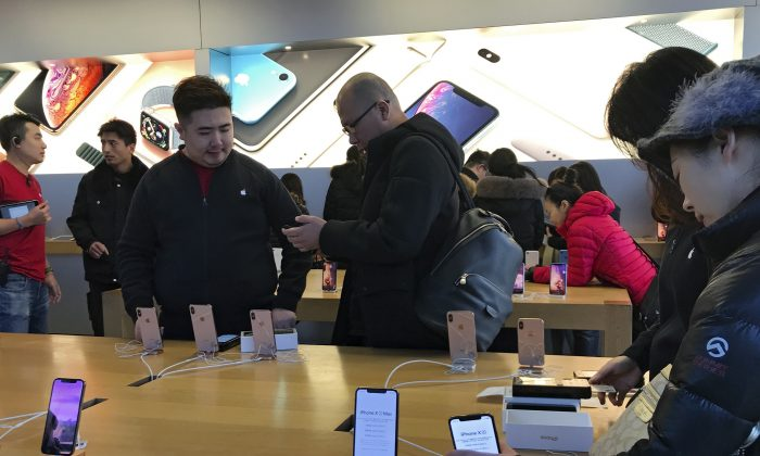 "People buy latest iPhone while others try out its latest model at an Apple Store in Beijing on Dec. 11, 2018. China is reportedly planning to ditch its ambitious tech manufacturing domination strategy under ""Made in China 2025"", as trade talks with the U.S. continue. (AP Photo/Andy Wong)"