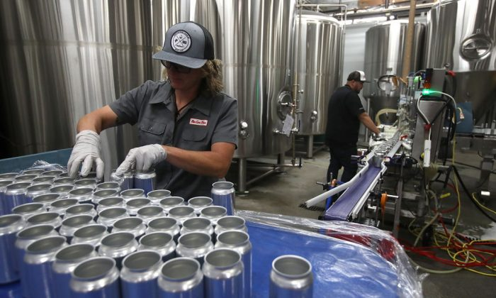 Kathryn Fisher with Can Van, a mobile canning company, places empty aluminum cans on a conveyor belt to be filled with beer at Devil's Canyon Brewery in San Carlos, California, on June 6, 2018. (Justin Sullivan/Getty Images)