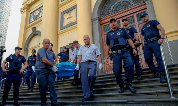 Municipal workers carry a corpse from the Cathedral of Campinas, 90 km northwest of Sao Paulo, Brazil, on Dec. 11, 2018. (Ari Ferreira/AFP/Getty Images)
