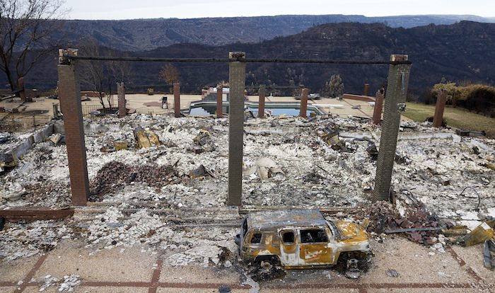 A vehicle rests in front of a home leveled by the Camp Fire in Paradise, Calif. on Dec. 3, 2018. (AP Photo/Noah Berger)