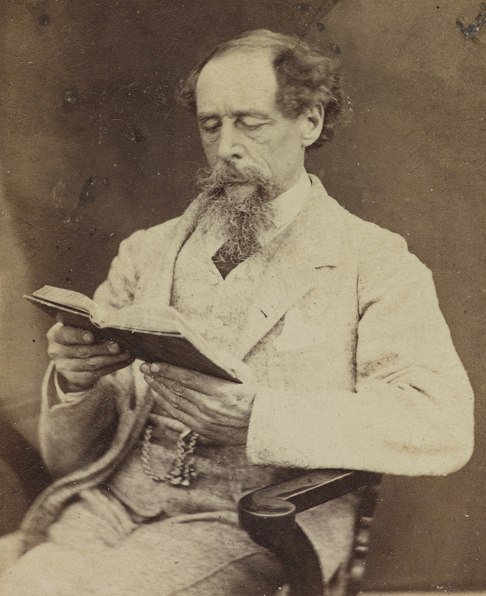 Charles Dickens reading a book