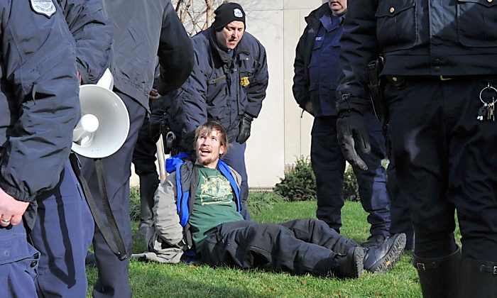 An arrested protester sits on the ground in Washington, on Jan. 19, 2012. (Karen Bleier/AFP/Getty Images)
