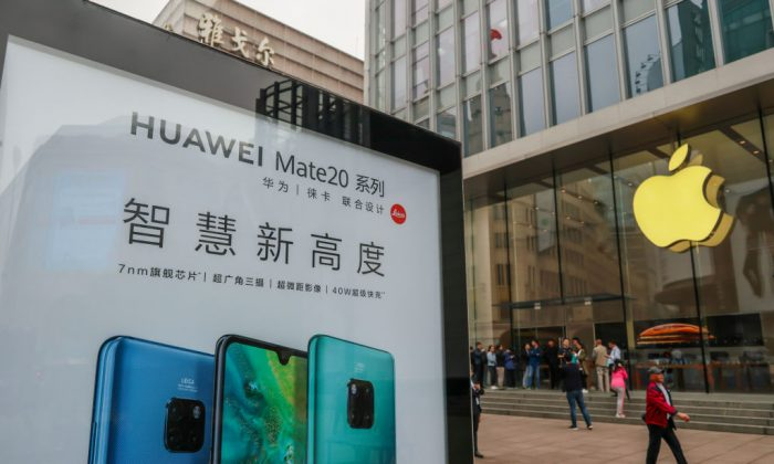 A Huawei poster is displayed outside an Apple store in Shanghai on Oct. 26, 2018. (STR/AFP/Getty Images)