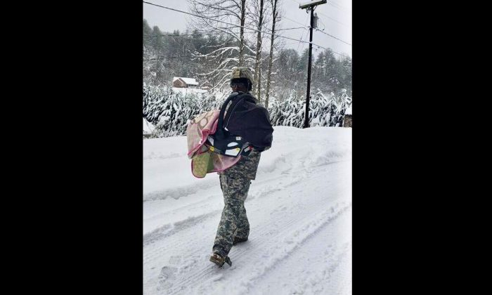 National Guard Sgt. Donovan McPherson, 27, was pictured carrying a baby during the massive snowstorm in North Carolina on Dec. 9, 2018. (North Carolina National Guard)