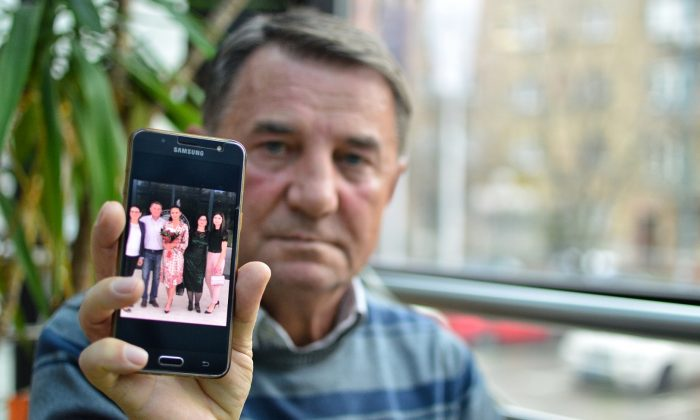 Fikret Grabovica, who lost one of his daughters during the siege of Sarajevo in 1993, shows a photo of his family.  (Antonio Cakshiri/Special to The Epoch Times)