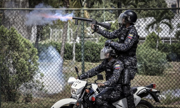 Venezuelan riot policemen shoot tear gas at students in Caracas on Nov. 21, 2018. Chinese technology companies are helping China's communist party to export surveillance tactics to the Maduro regime. (YURI CORTEZ/AFP/Getty Images)