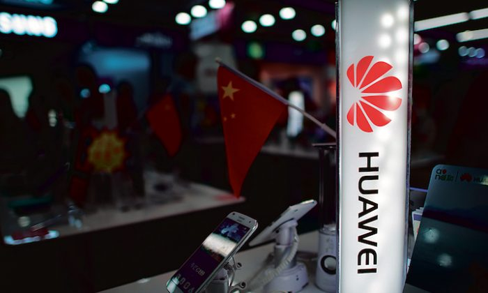 A logo of Huawei next to a Chinese flag in Shanghai on Oct. 1, 2014. (JOHANNES EISELE/AFP/Getty Images)