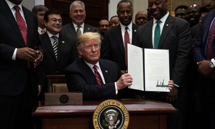 President Donald Trump participates in signing an executive order to establish the White House Opportunity and Revitalization Council as Secretary of Housing and Urban Development Secretary Ben Carson and Sen. Tim Scott (R-S.C.) look on at the Roosevelt Room of the White House in Washington, on Dec. 12, 2018. (Alex Wong/Getty Images)