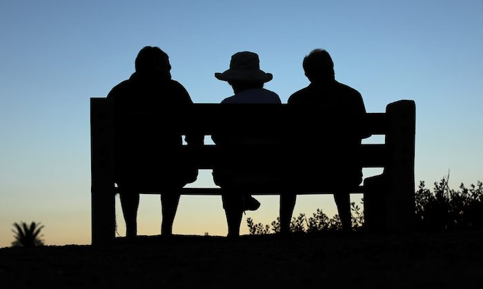 Elderly people sit on a park bench after sun set in Encinitas, California, on July 5, 2017. (Reuters/Mike Blake)
