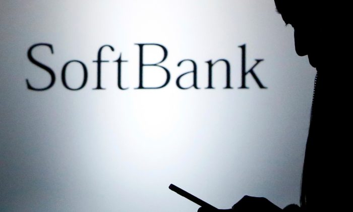 A pedestrian holding a mobile phone walks past a logo of SoftBank Corp in front of its branch in Tokyo on Dec. 31, 2013. (Yuya Shino/Reuters)