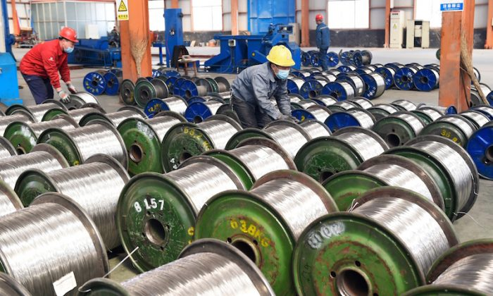 """Workers move rolls of aluminum at a factory in Zouping in China's eastern Shandong province on April 7, 2018.  China said on April 6 it is ready to pay """"any cost"""" in a trade war after U.S. President Donald Trump threatened an additional $100 billion in tit-for-tat tariffs on Beijing. (AFP/Getty Images)"""