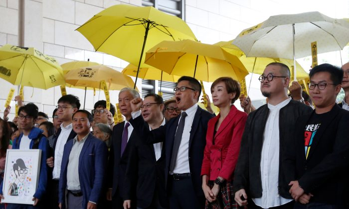 (L-R) Pro-democracy activists Chung Yiu-wa, Cheung Sau-yin, Lee Wing-tat, Chu Yiu-ming, Benny Tai, Chan Kin-man, Tanya Chan, Shiu Ka-chun, and  Raphael Wong pose outside a court in Hong Kong, China Nov. 19, 2018. (Bobby Yip/Reuters)