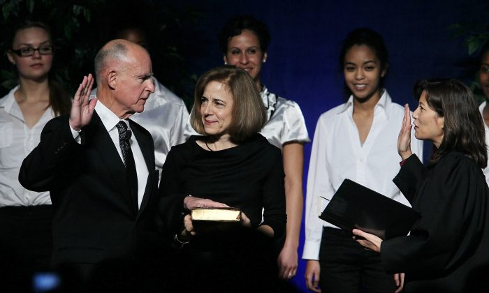 California Chief Justice Tani Cantil-Sakauye (R) swears in Jerry Brown (L) as governor, as Brown's wife, Anne Gust-Brown (C), looks on, in Sacramento, Calif., on Jan. 3, 2011. (Justin Sullivan/Getty Images)