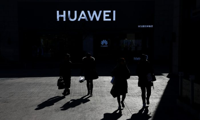 People walk past a Huawei shop in Beijing on Dec. 11, 2018. (Thomas Peter/Reuters)