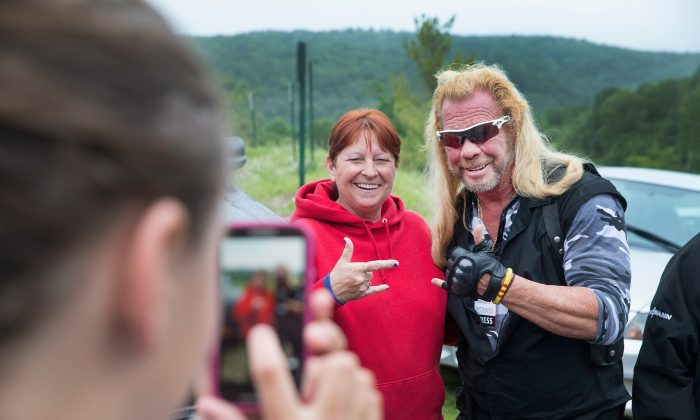 Dog the Bounty Hunter, Duane Chapman poses with a fan outside of a press conference where  New York Governor Andrew Cuomo, was speaking to the media about the capture of convicted murderer David Sweat in Malone, New York, on June 28, 2015. (Scott Olson/Getty Images)