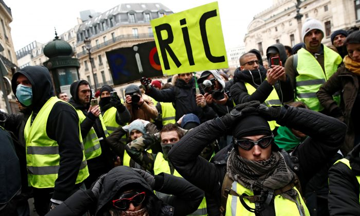 Protesters wearing yellow vests kneel on the street as they gather in front of the Opera House as part of the 'yellow vests' movement in Paris on Dec. 15, 2018. (Reuters/Christian Hartmann)