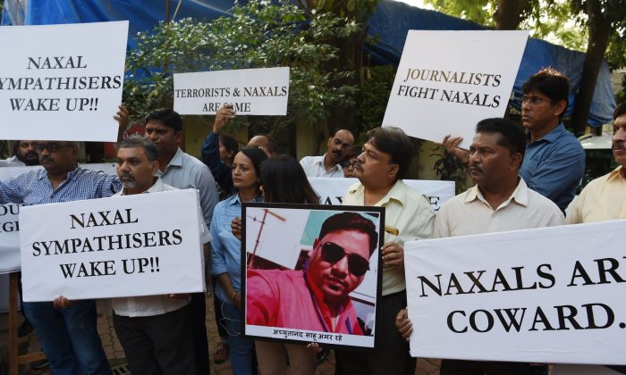 Journalists wearing black arm-bands hold placards and a photograph of journalist Achyuta Nanda Sahu, who was killed by a Maoist ambush while working, during a protest meeting to condemn the killing of Achyuta, in Mumbai on November 1, 2018. Sahu, a cameraman with Indian state run TV news channel Doordarshan was killed in a Maoist attack in Dantewada district in central Indian state of Chhattisgarh during an ambush. (Indranil Mukherjee / AFP)