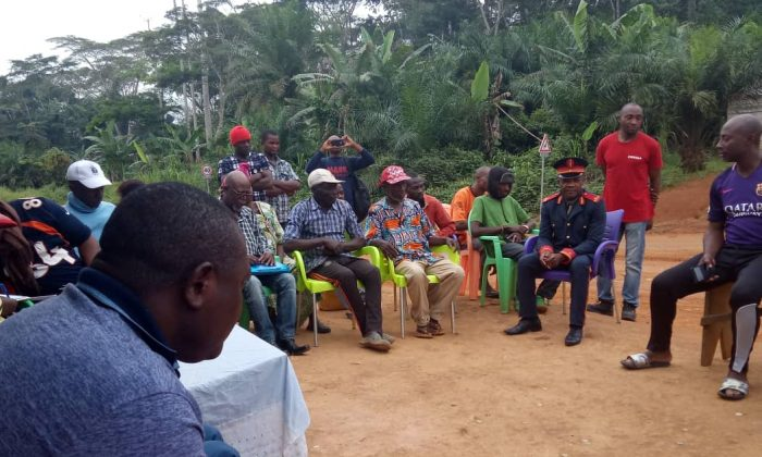 Civil society activists listen to members of the indigenous community affected by the Sudcam project in south of Cameroon on Nov. 18, 2018. The uniformed man is Akoumba Akoumba, a traditional. (By Amindeh Blaise Atabong/Special to The Epoch Times)