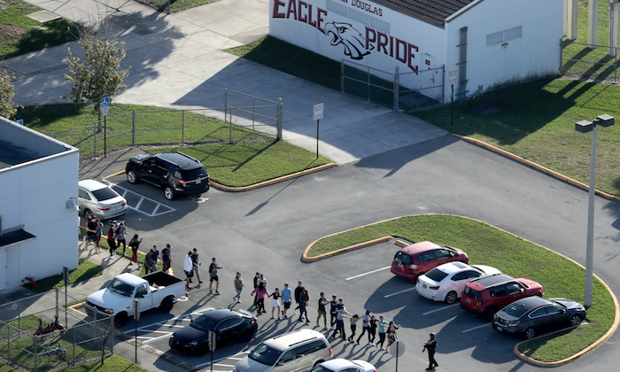Students are evacuated by police from Marjory Stoneman Douglas High School in Parkland, Fla., after a shooter opened fire on the campus, on Feb. 14, 2018. (Mike Stocker/South Florida Sun-Sentinel via AP)