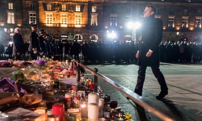 French President Emmanuel Macron stands at a monument near the Christmas market in Strasbourg's Kleber square, used as a makeshift memorial for the victims of the Dec. 11 attack that killed four people. (Pool/AFP/Getty Images)