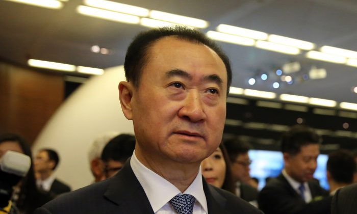 Wang Jianlin (C), CEO of Dalian Wanda Commercial Properties Co. arrives for the company's IPO at the Hong Kong stock exchange on December 23, 2014. (Isaac Lawrence/AFP/Getty Images)