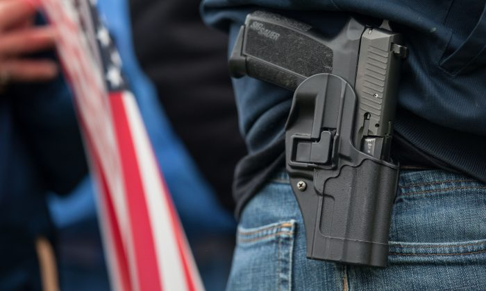 A demonstrator carries a handgun while listening to speakers at a pro-gun rally in Olympia, Wash., on Jan. 19, 2013. (David Ryder/Getty Images)