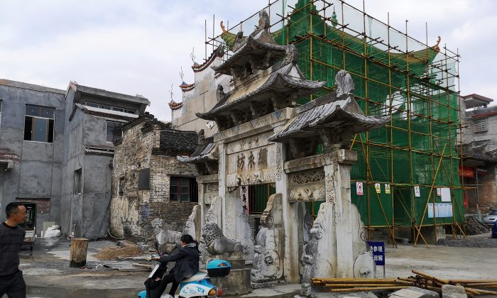 A woman rides a motorcycle past an imperial-style arch and a building under renovation in Rucheng county, Hunan Province, China on Dec. 3, 2018. (Shu Zhang/Reuters)