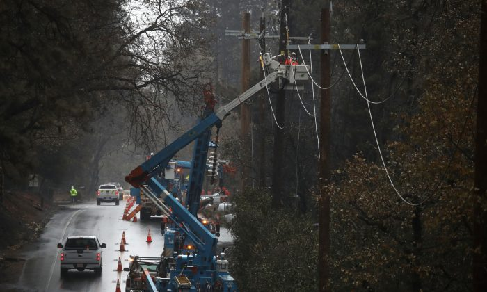 Pacific Gas and Electric (PG&E) crews repair power lines that were destroyed by the Camp Fire on November 21, 2018 in Paradise, California. (Photo by Justin Sullivan/Getty Images)