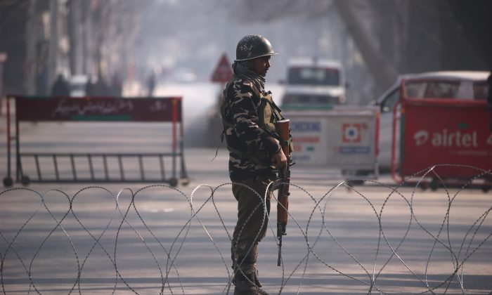An Indian policeman stands guard behind concertina wire laid across a road leading to the Indian army headquarters in Srinagar on Dec. 17, 2018. (Danish Ismail/Reuters)
