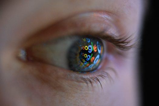 An image of the Google logo is reflected on the eye of a man in London