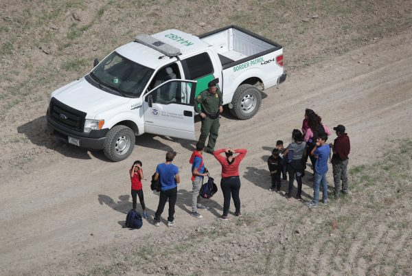 Illegal aliens turn themselves in to a Border Patrol agent after crossing from Mexico into the United States in Mission, Texas, on Nov. 7, 2018. (John Moore/Getty Images)