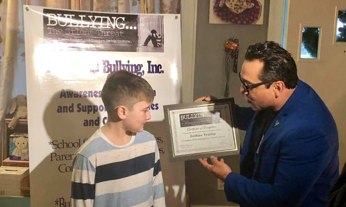 Teach Anti Bullying founder Claudio Cerullo gives an award to Joshua Trump, a Delaware 11-year-old who was bullied for years over his last name, on Dec. 15, 2018. (Teach Anti Bullying)