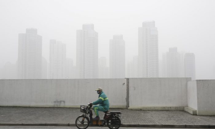 A man wearing a face mask rides an electric bicycle near the financial district of Pudong amid heavy smog in Shanghai, China on Dec. 23, 2015. (Aly Song/Reuters)