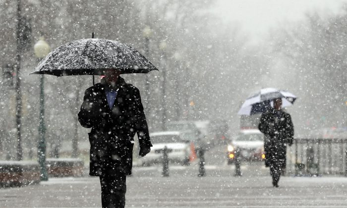 File—People arriving at the Capitol Building in Washington, on Dec. 10, 2013, as snow falls. Some climate experts say polar vortex disruption could bring unusually foul weather to parts of the United States. (Pablo Martinez Monsivais/AP Photo)
