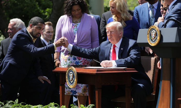 President Donald Trump shakes hands with Pastor Darrell Scott, co-founder of the New Spirit Revival Center, before Trump signs an executive order during an event in the Rose Garden to mark the National Day of Prayer at the White House on May 3, 2018. (Chip Somodevilla/Getty Images)