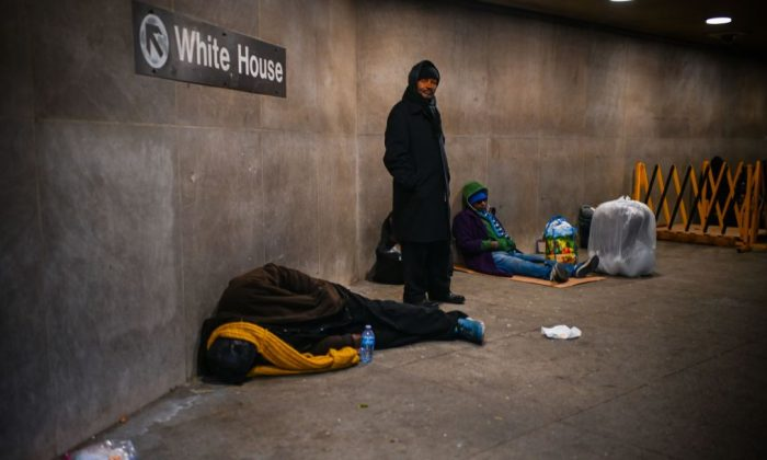 A homeless person sleeps below a sign indicating the exit to the White House at McPherson Square Metro station in Washington, D.C, on Dec. 12, 2018. (Eric Baradat/AFP/Getty Images)