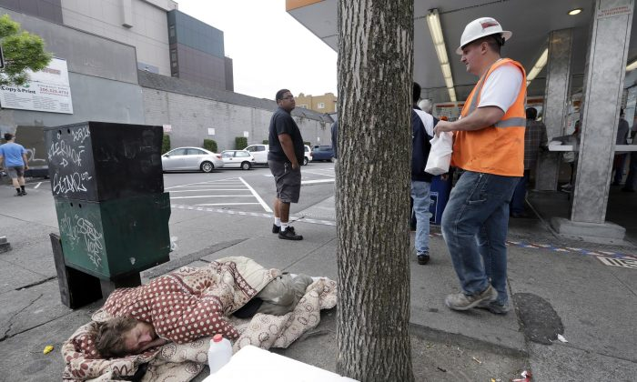 A man sleeps on the sidewalk as people behind line-up to buy lunch at a Dick's Drive-In restaurant in Seattle, on May 24, 2018. (Elaine Thompson/AP)