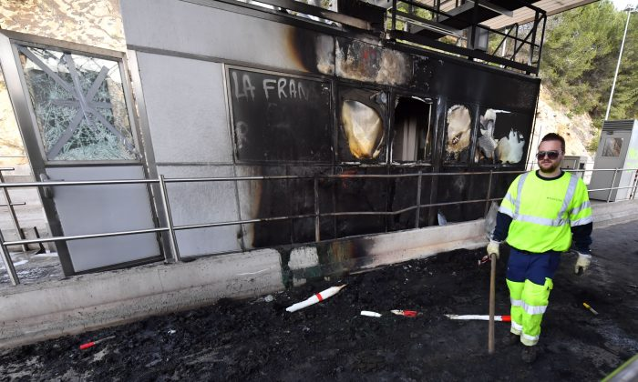 A worker of French construction group Vinci stands near a damaged payment booth a day after the highway toll was set on fire in Bandol, near Marseille, southern France on Dec. 18, 2018. (Gerard Julien/AFP/Getty Images)