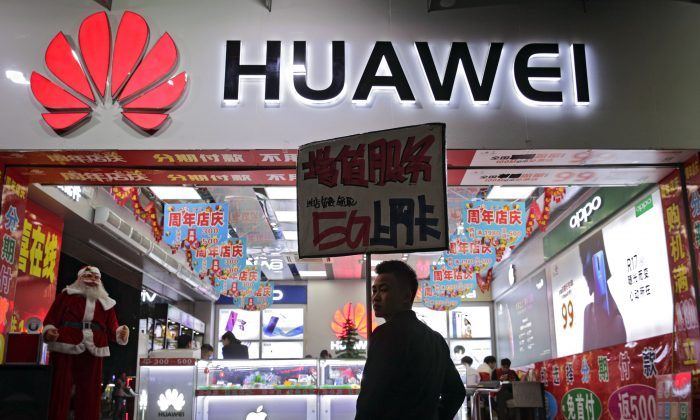 A worker holds a sign promoting a sale for Huawei 5G internet services at a mobile phone retail shop in Shenzhen, China, on Dec. 18, 2018. (AP Photo/Andy Wong)