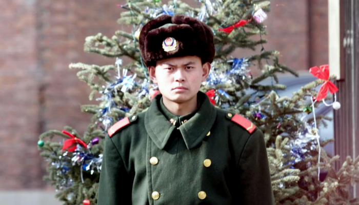 A Chinese People's Armed policeman stands guard in front of a Christmas tree outside a diplomatic compound in Beijing 21, China on Dec. 2000. (Goh Chai Hin/AFP/Getty Images)