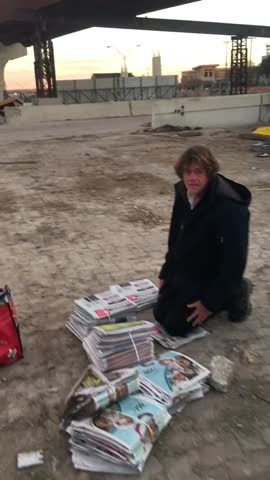 homeless man with newspapers