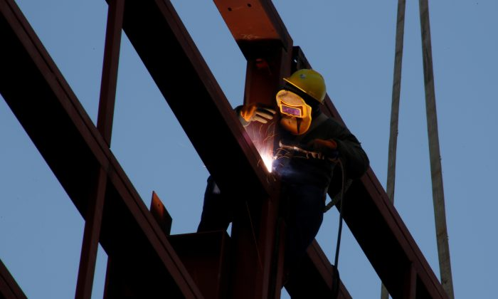 A worker welds as he stands on the metal frame of a building at a construction site in Beijing on Dec. 12, 2018. (Thomas Peter/Reuters)