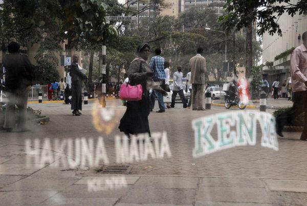 Kenyans walk past a store with a Hakuna Matata sign
