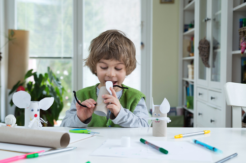 Little boy being creative making homemade do-it-yourself paper toys. Supporting creativity, learning by doing, learning through experience. Helping child gain access to a creative way of seeing. (Shutterstock)